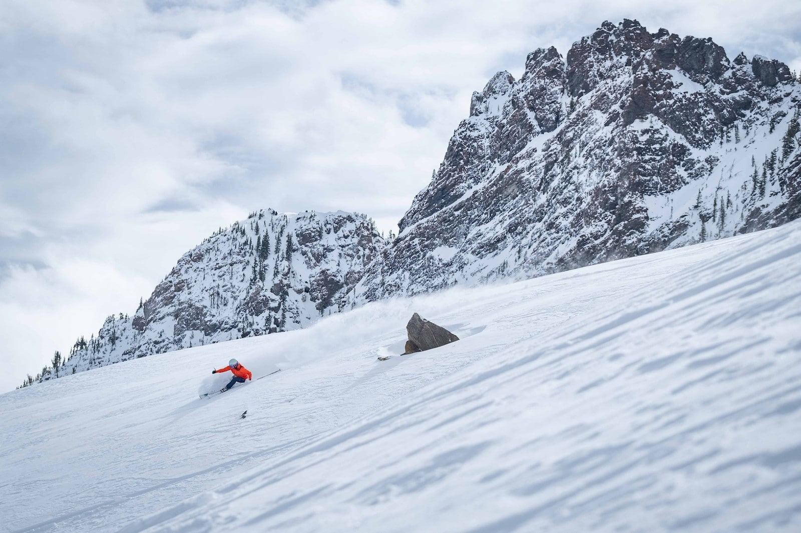 Image of a skier in orange shredding down a mountain at Alta Ski Area in Utah