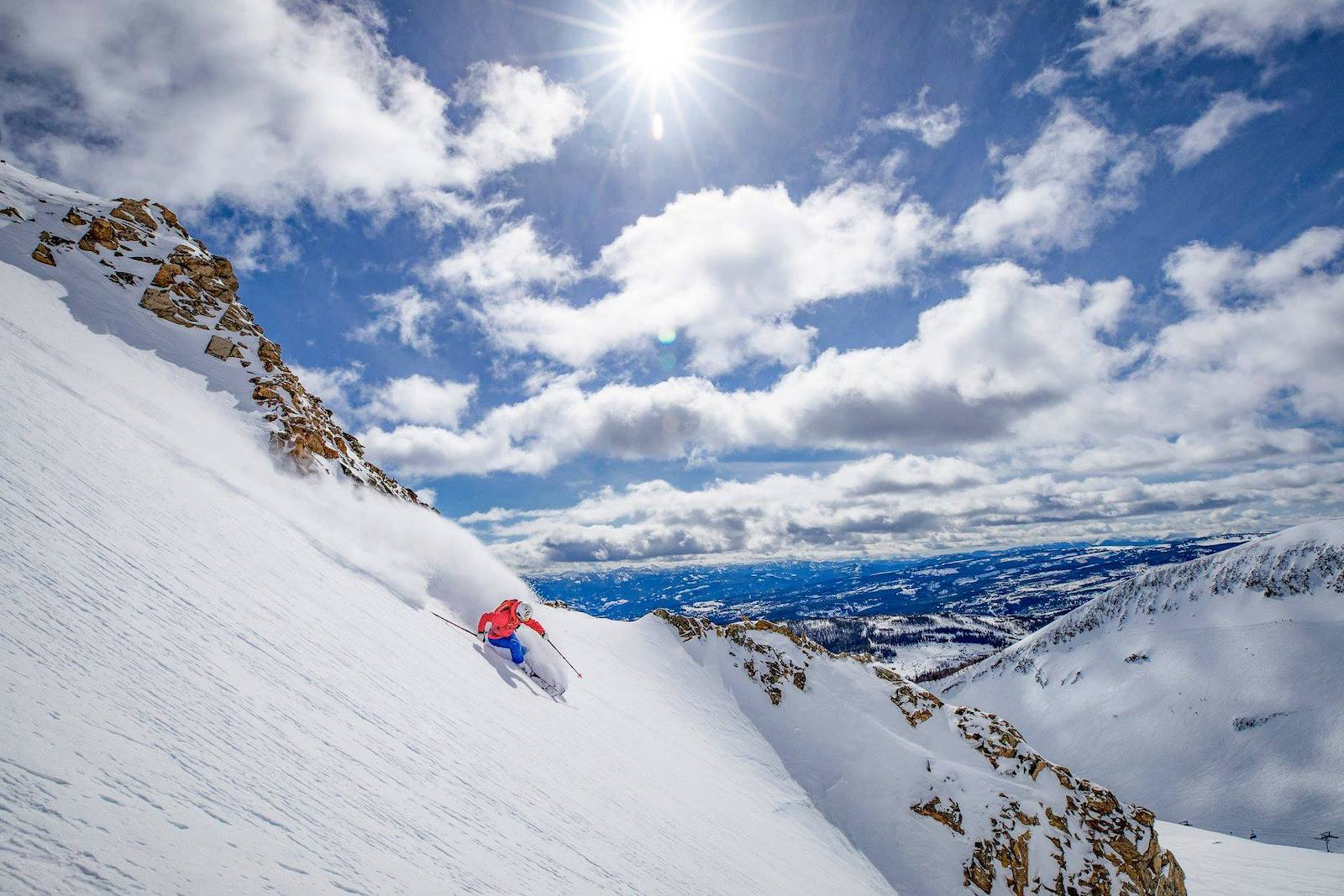 Image of a skier in red hitting the slopes at Big Sky Ski Resort in Montana on a bluebird day