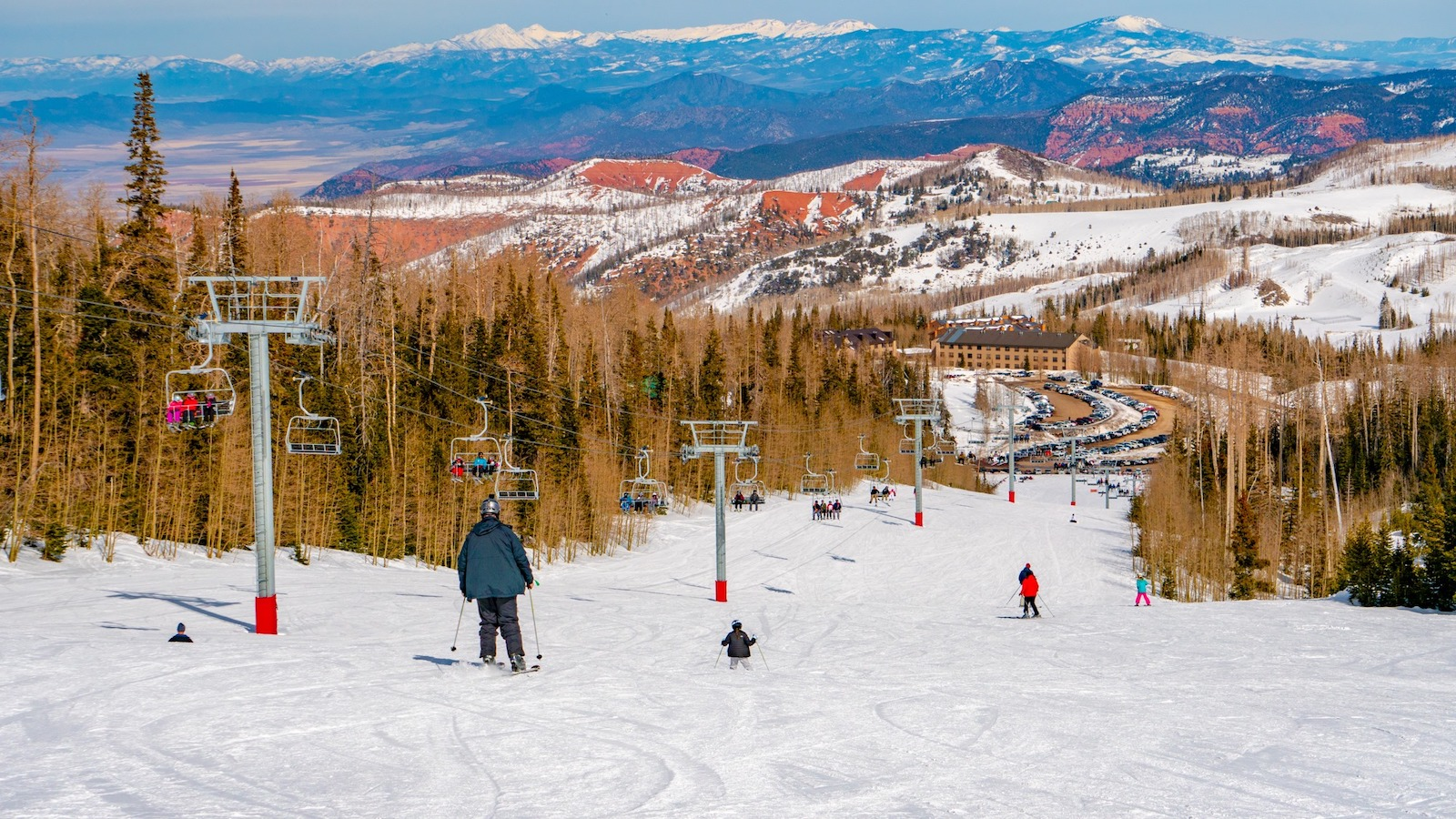 Image of skiers going down the slopes near the chairlift at Brian Head Resort in Utah