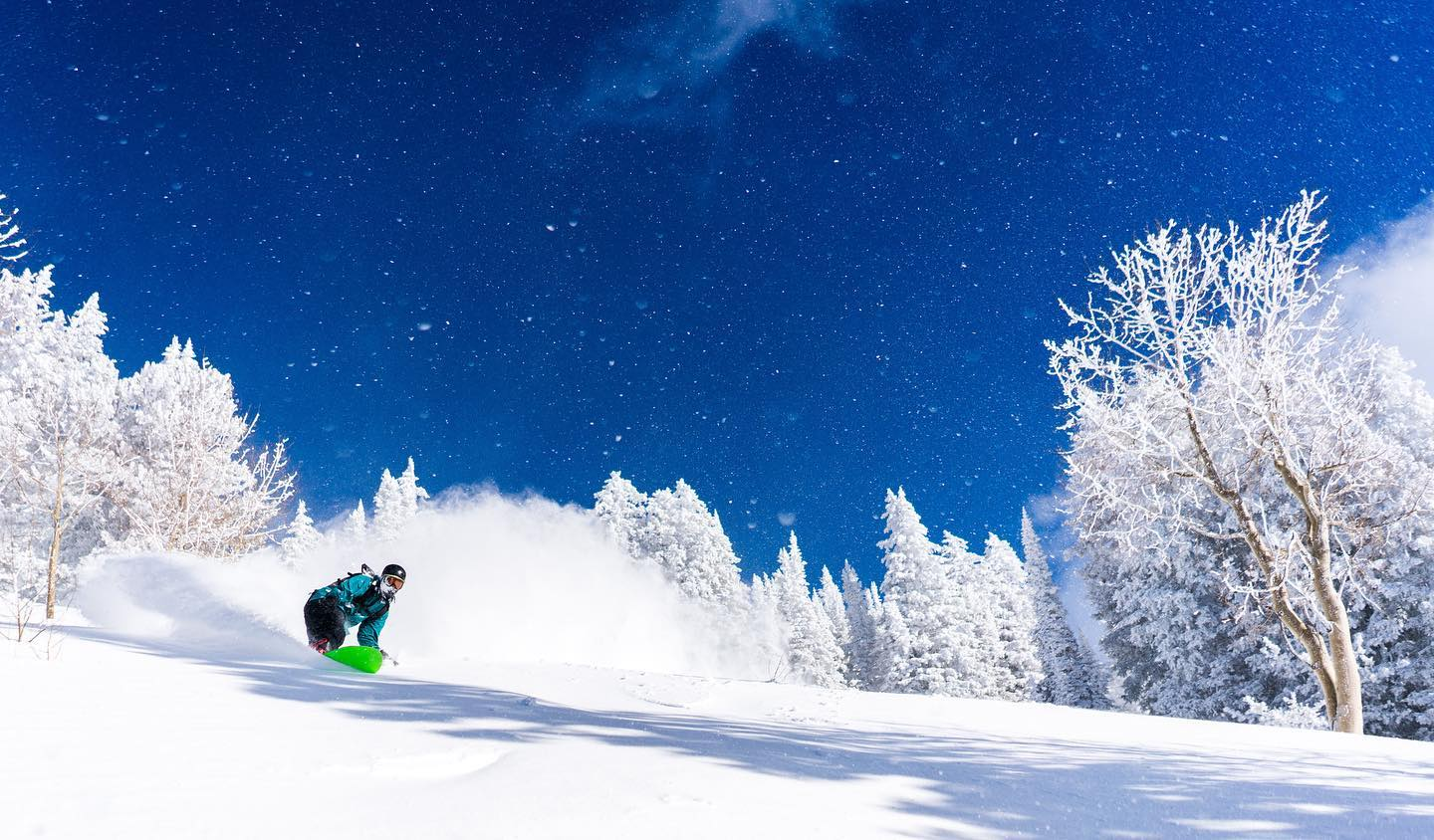 Image of a snowboarder with a neon green board hitting the slopes under a starry sky at Brighton Resort in Utah