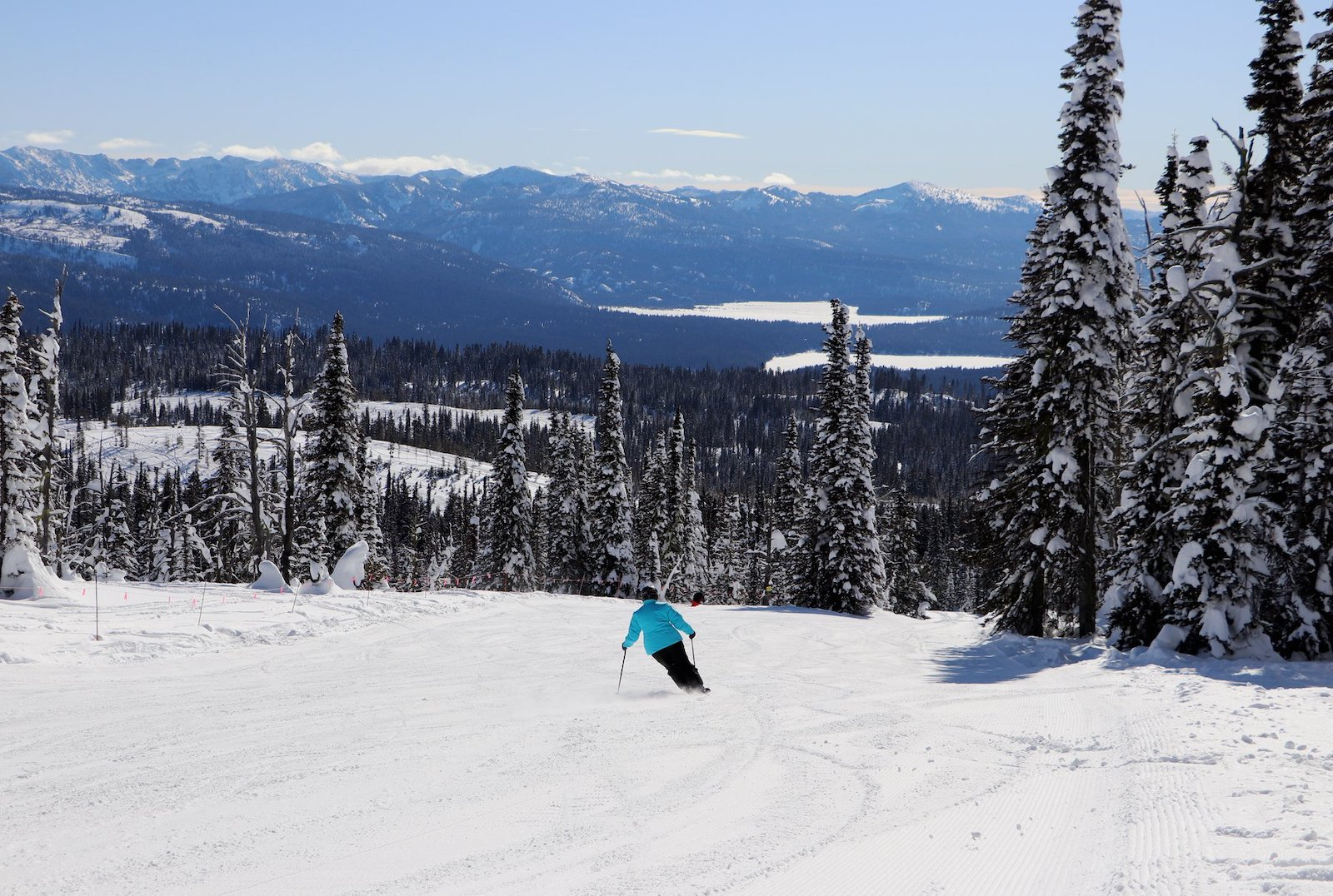 Image of a solo skier in blue going down the slopes at Brundage Mountain Ski Resort in Idaho