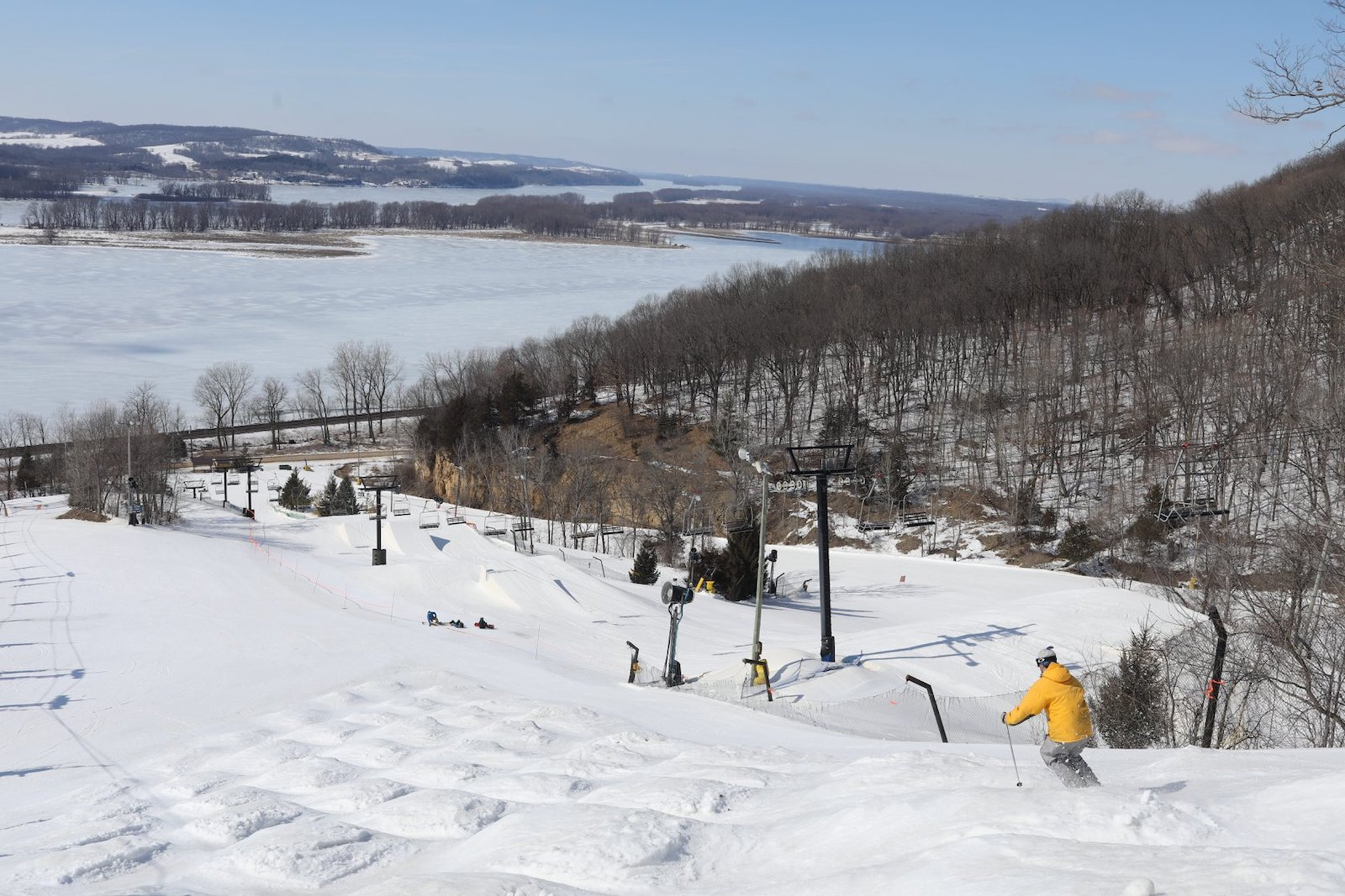 Image of skier in yellow coat going down the slopes at Chestnut Mountain Resort in Illinois
