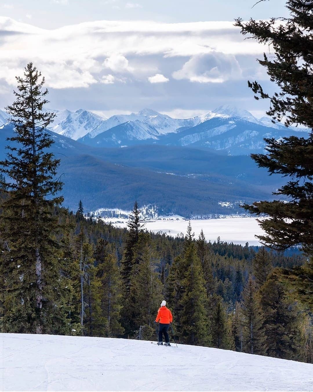 Image of a skier in orange looking out at the mountains at Discovery Ski Area in Montana
