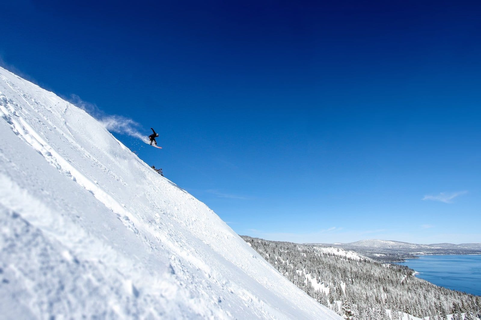 Image of a snowboarder jumping of the slopes at Homewood Mountain Resort in Califonia