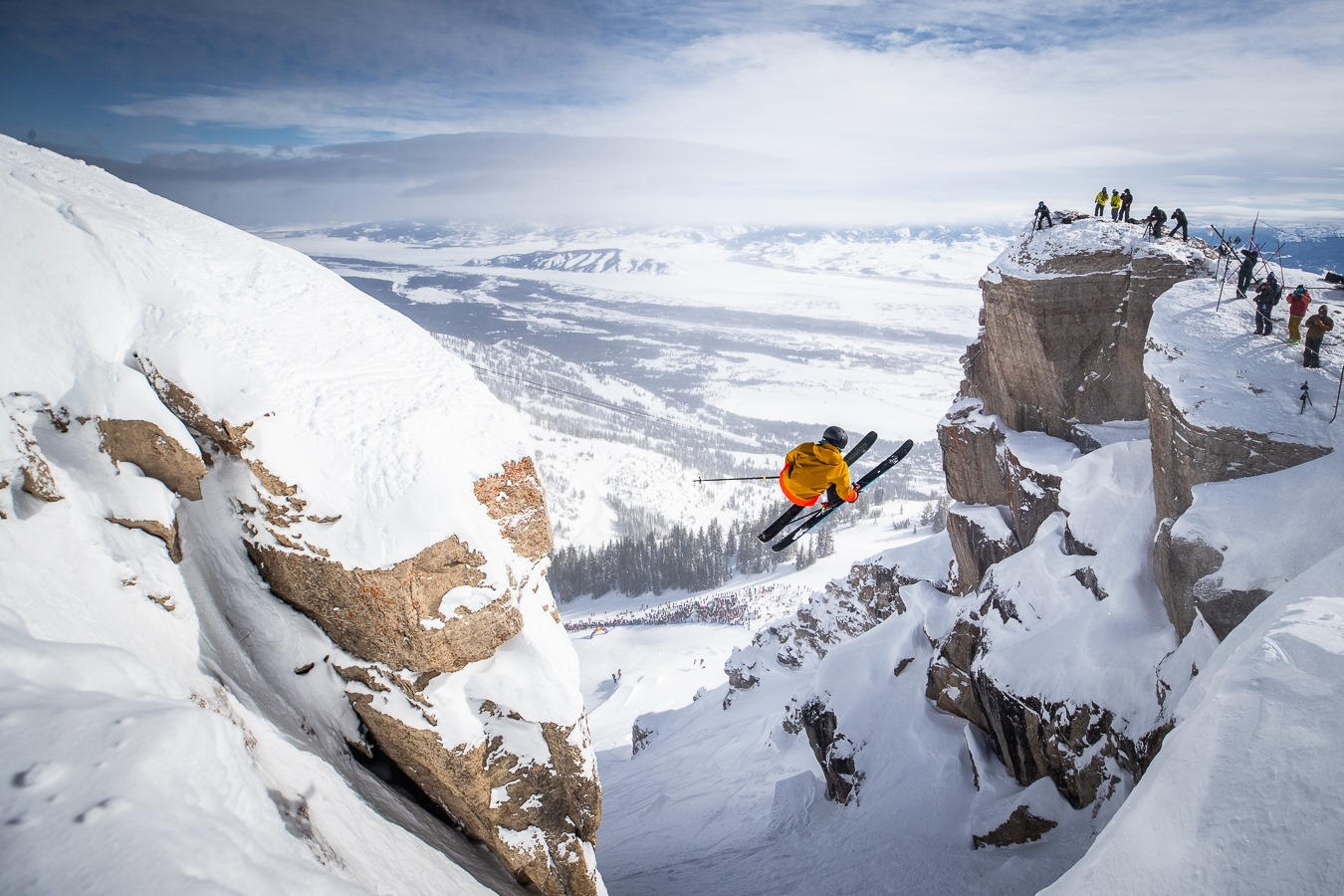 Image of a skier in orange making a massive jump between snow covered rocks at Jackson Hole Mountain Resort in Wyoming