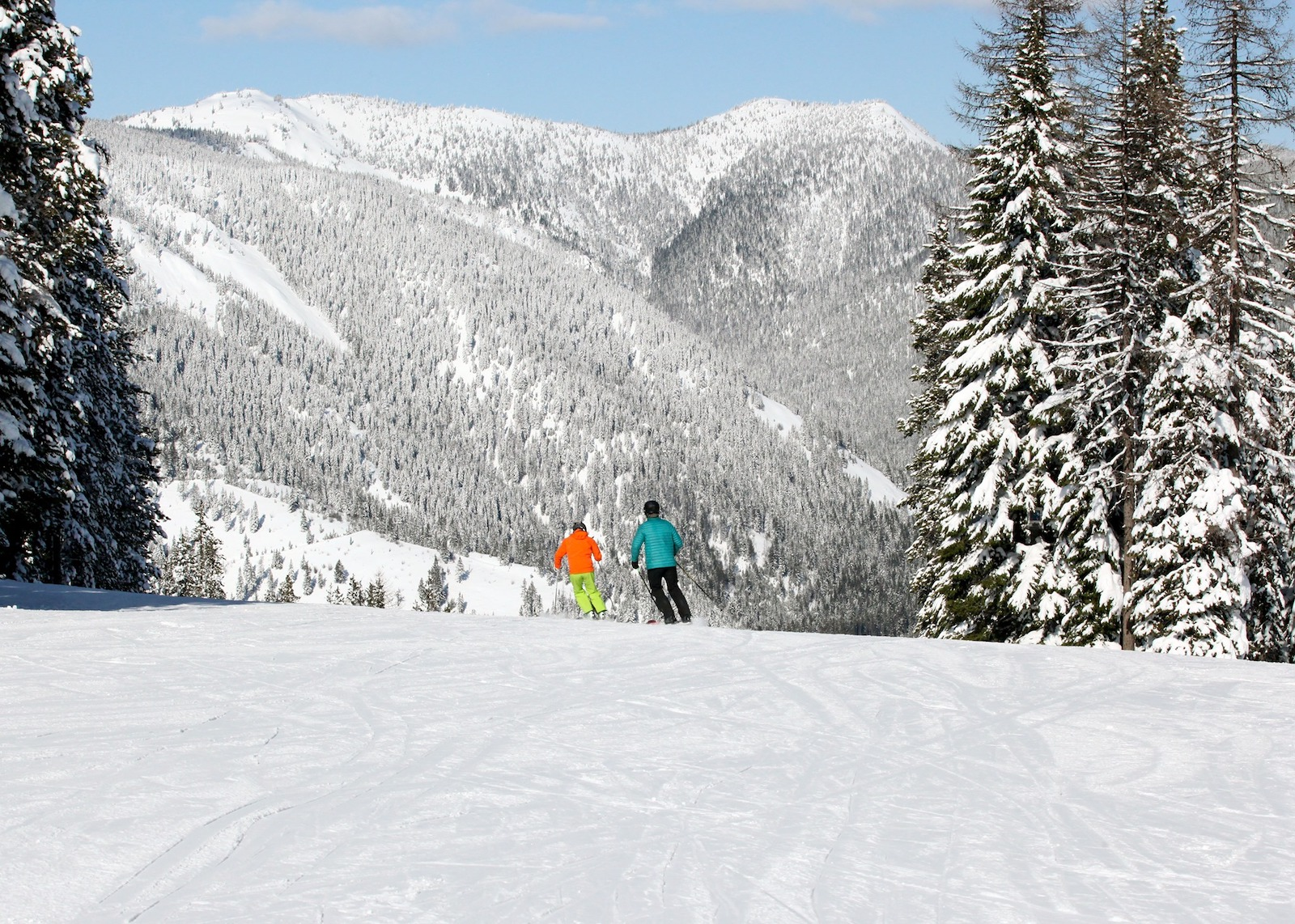 Image of 2 skiers in orange, green and teal, going down the slopes at Lookout Pass Ski Area in Idaho