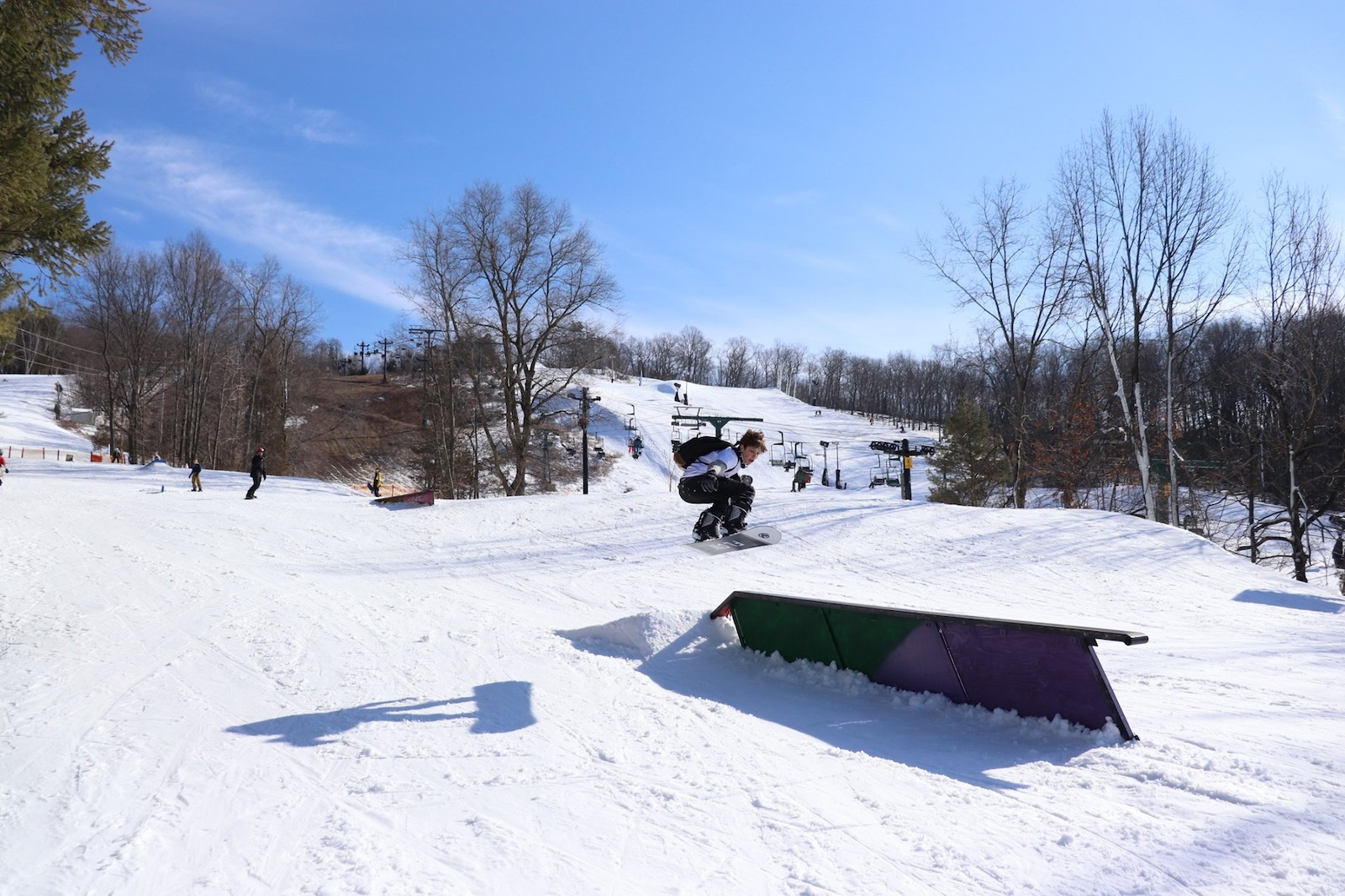 Image of a snowboarder jumping onto a rail at the terrain park at Mount Peter in New York