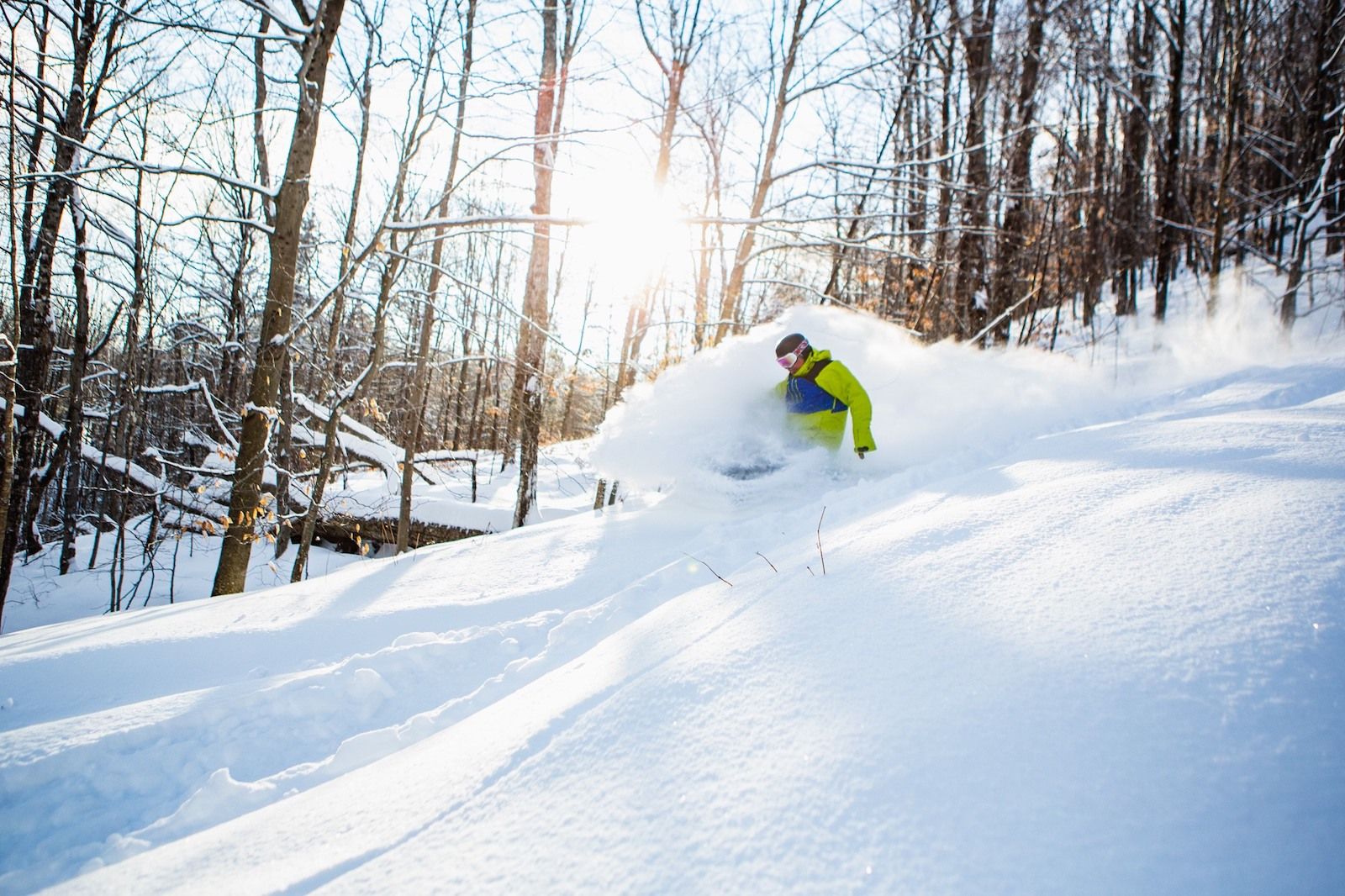 Image of a snowboarder in green shredding powdery snow at Mt. Abram Ski Area in Maine
