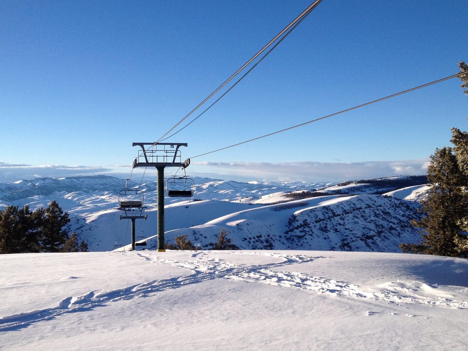 Image of chair lifts at Pine Creek Ski Resort in Wyoming surrounded by scenic views