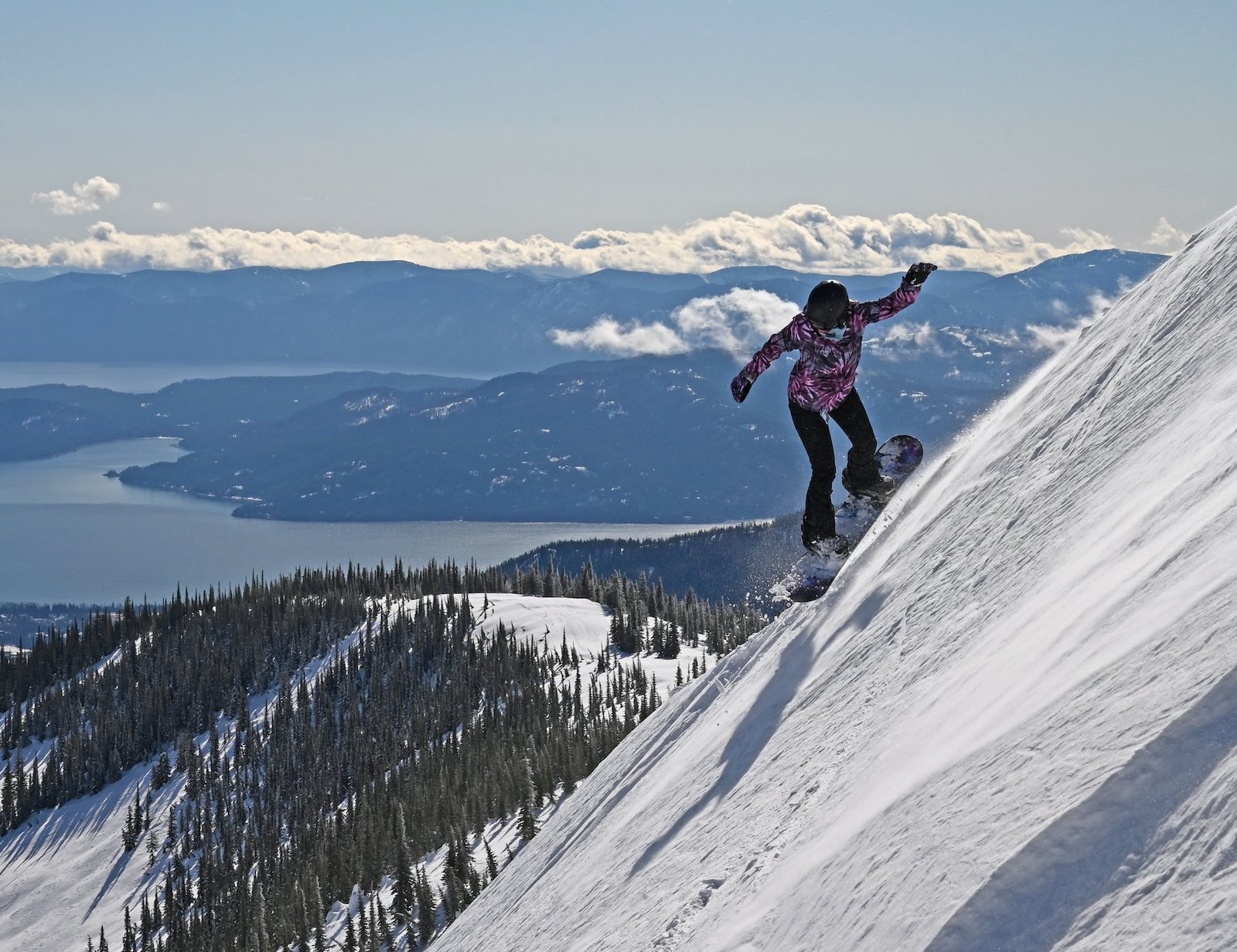 Image of a snowboarder jumping down a sharp incline at Schweitzer Mountain Resort in Idaho
