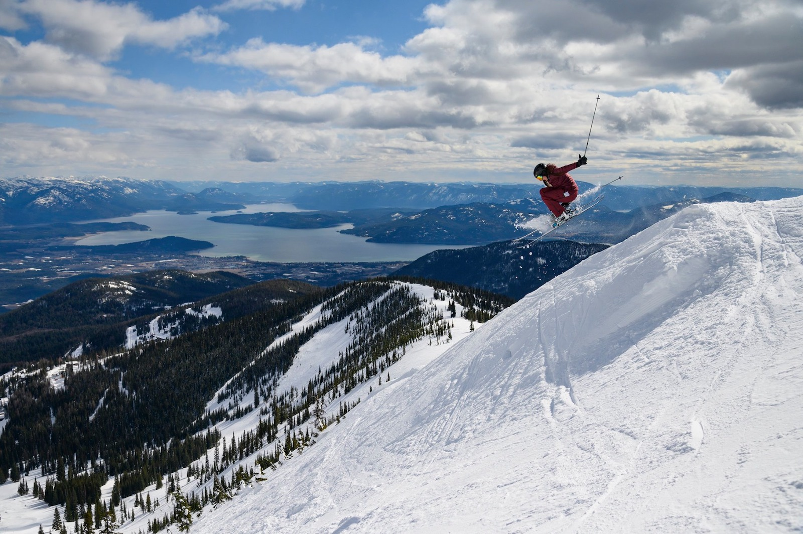 Image of as skier in red jumping catching air at Schweitzer Mountain Resort in Idaho
