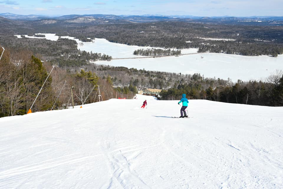 Image of skiers going down the slopes at Shawnee Peak Ski Area in Maine