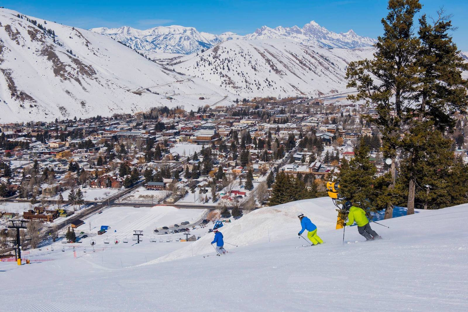 Image of skiers going down the slopes overlooking the city of Jackson at Snow King Mountain Resort in Wyoming