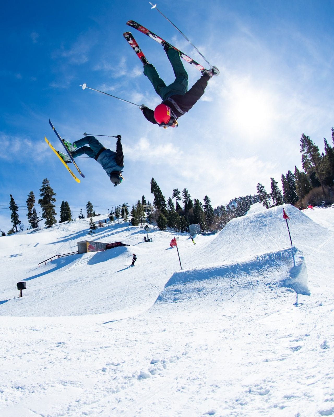 Image of two skiers doing a backflip off a ramp at Snow Summit Ski Resort in California