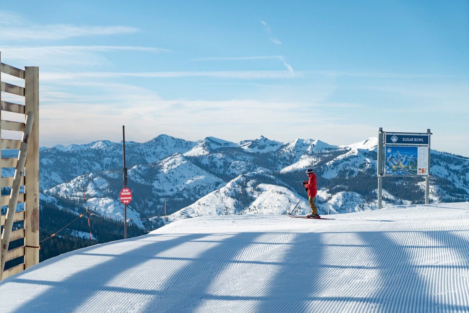Image of a skier in red at Sugar Bowl Resort in California at the top of the slope looking over the mountains