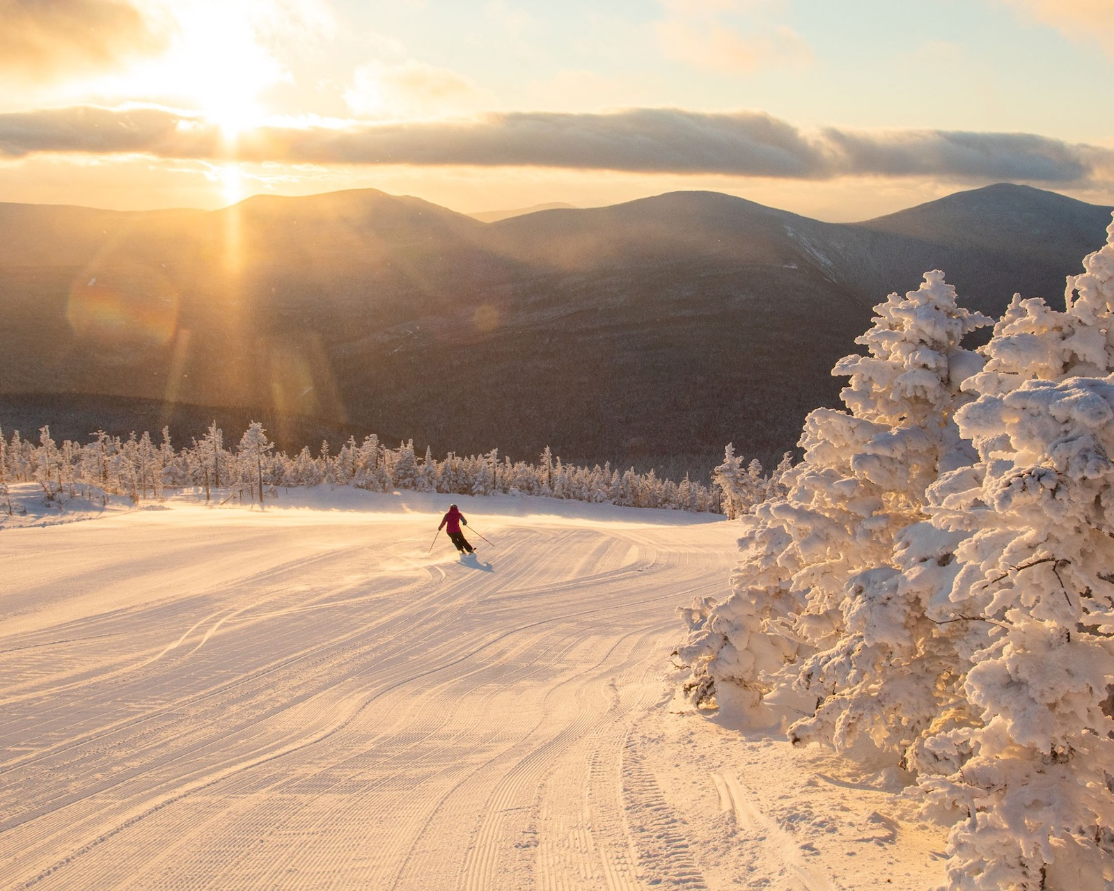 Image of a skier going down the slopes surrounded by mountain views and golden light at Sugarloaf Ski Resort in Maine