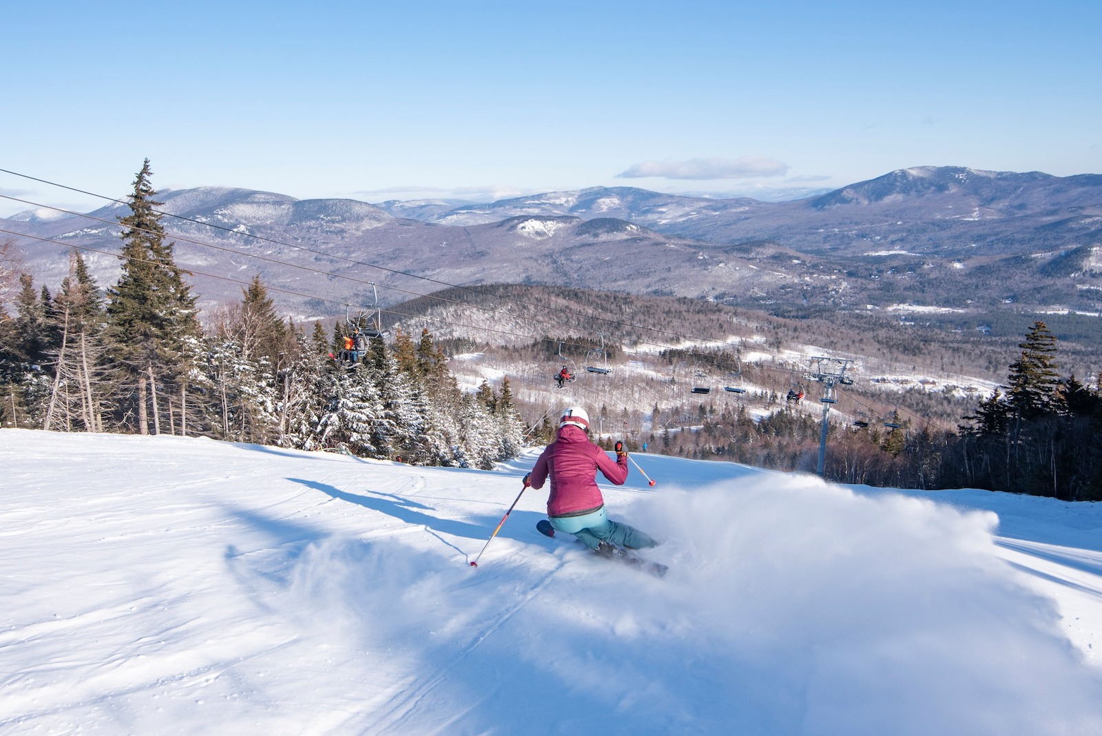 Image of a skier in pink going down the slopes at Sunday River Ski Resort in Maine