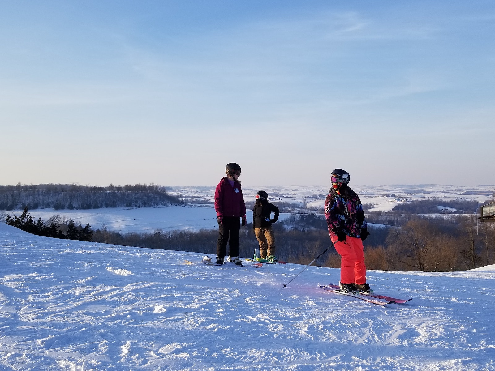 Image of three skiers and the top of the slope at Sundown Mountain Resort in Iowa