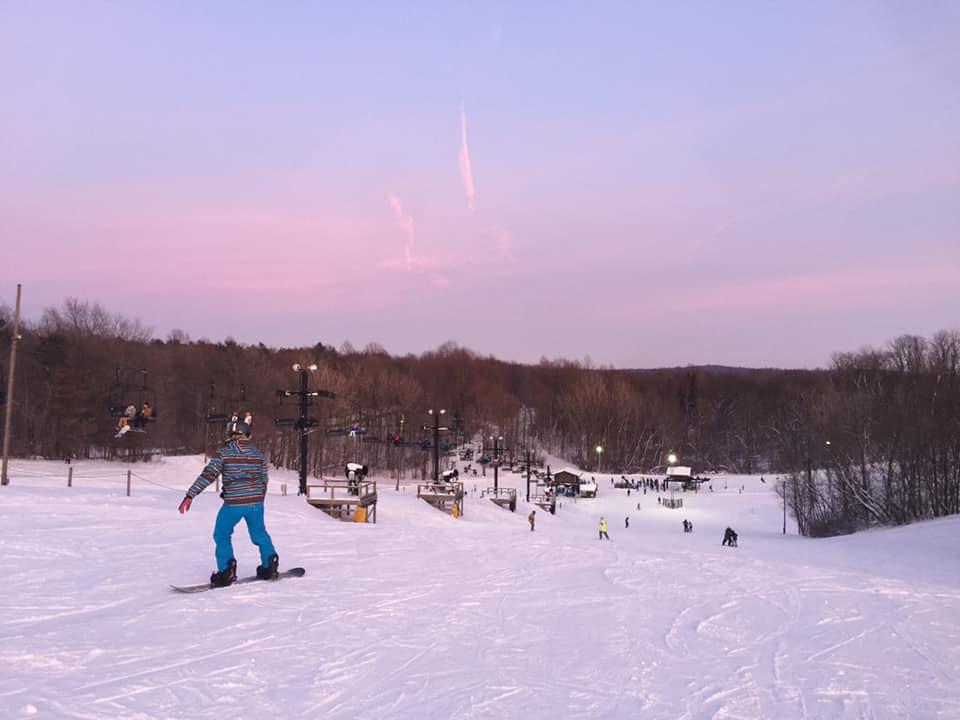 Image of a snowboarder riding at dawn at Swiss Valley Ski and Snowboard Area in Michigan
