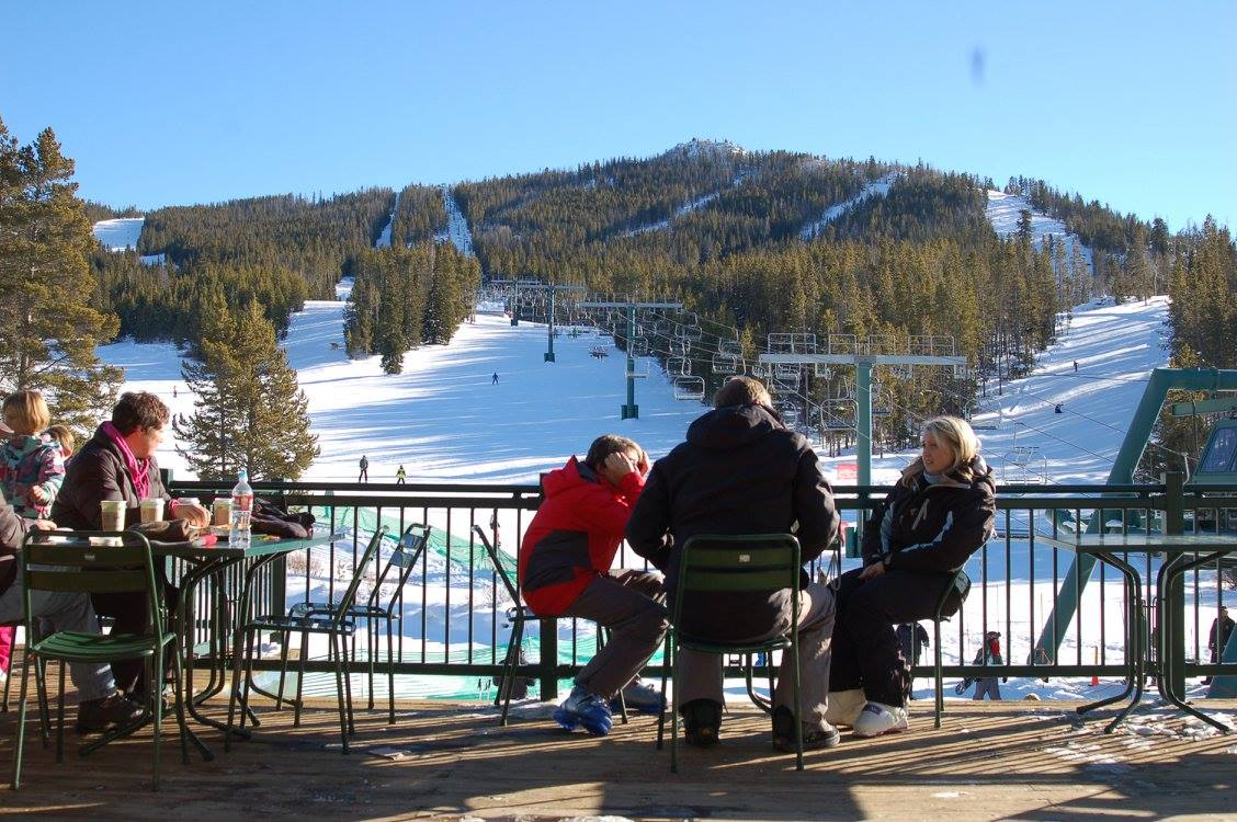 Image of guests sitting on a deck looking out at White Pine Ski Resort in Wyoming