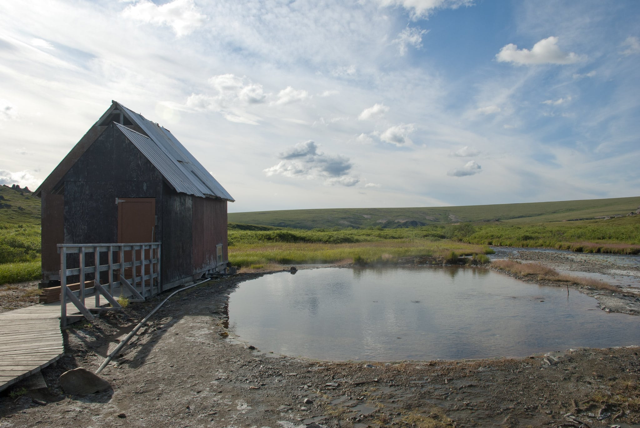 Image of a bathhouse and outdoor hot spring at Serpentine Hot Springs, Alaska