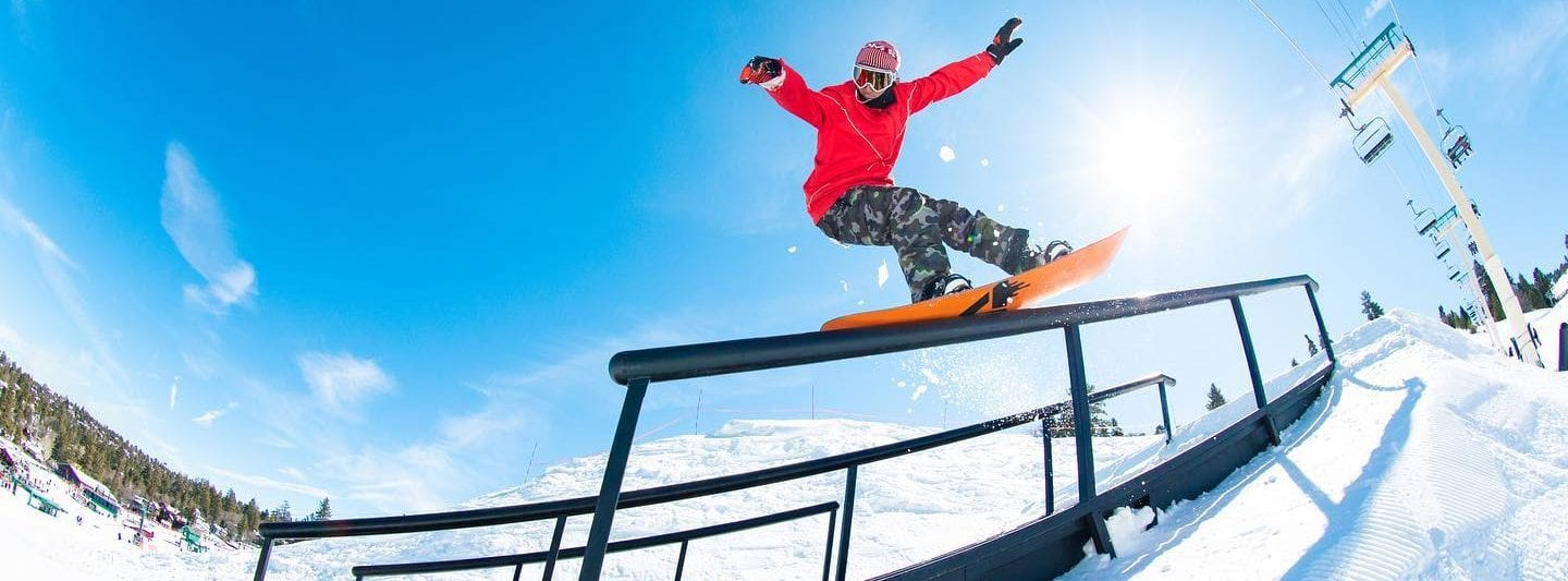 Image of snowboarder in a red coat riding down the rail at the terrain park at big bear mountain resort California