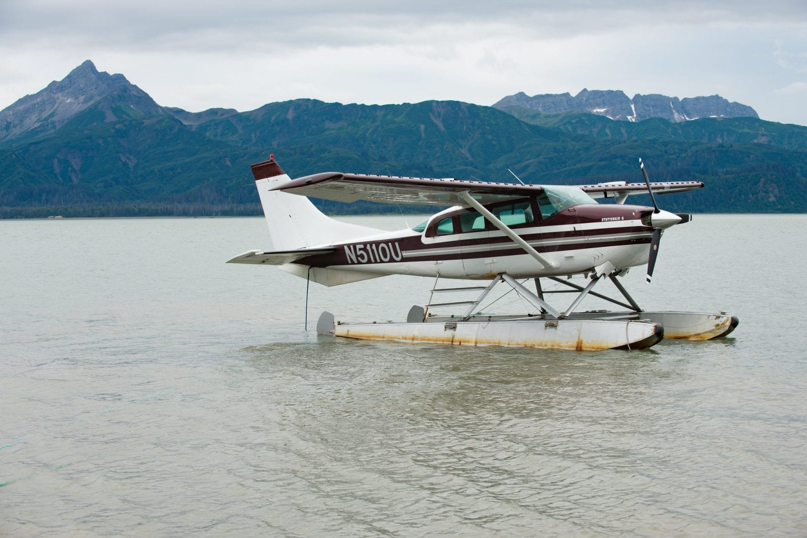 Image of a seaplane in the water in front of mountains