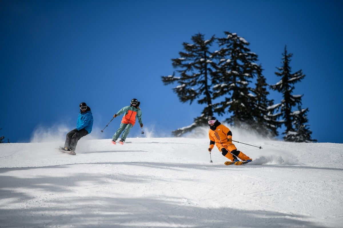 Image of two skiers and one snowboarder at Grouse Mountain in Canada