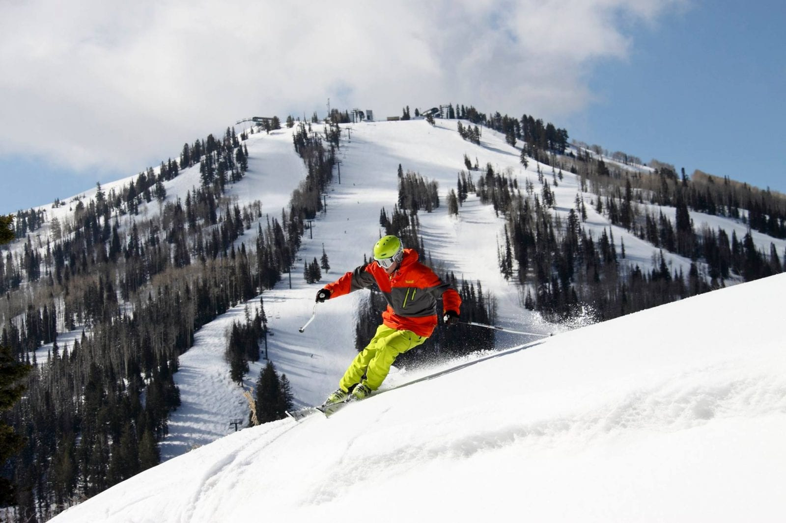 Skier wearing bright colors, going down the slopes at Deer Valley Resort in Utah
