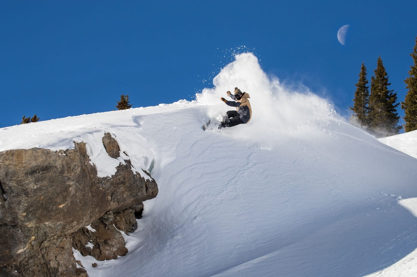 Image of a snowboarder jumping off a rock formation at Snowbird in Utah