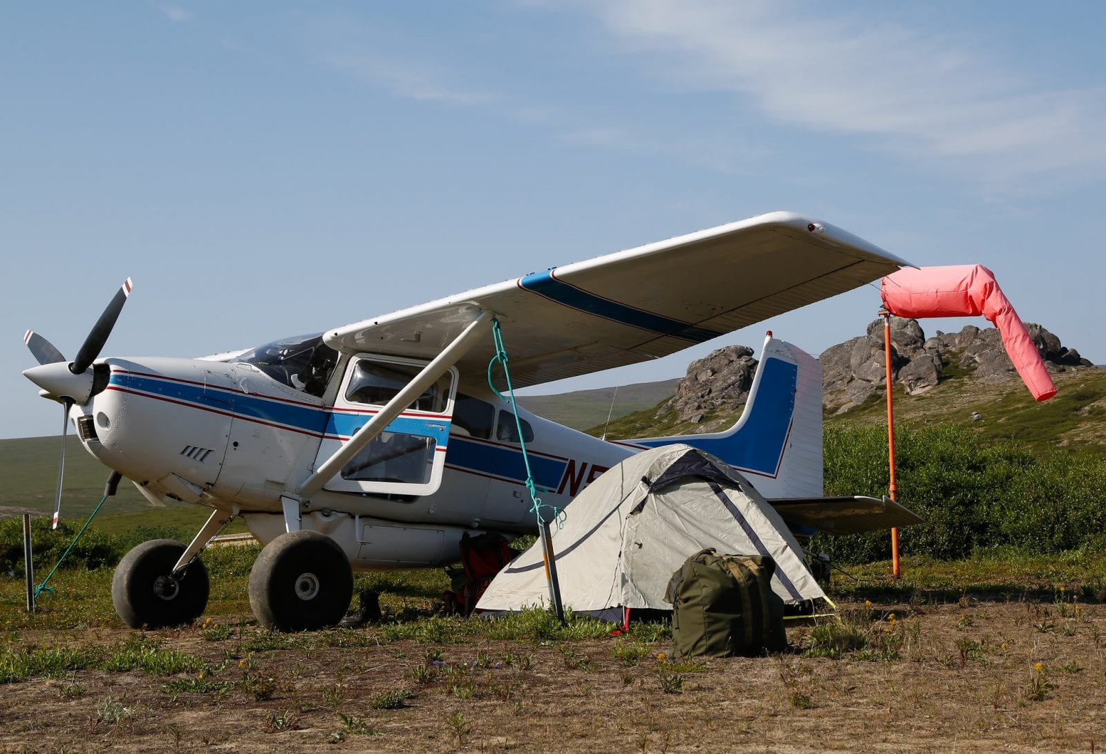Image of a charter plan and tent underneath the plane wing at Serpentine Hot Springs