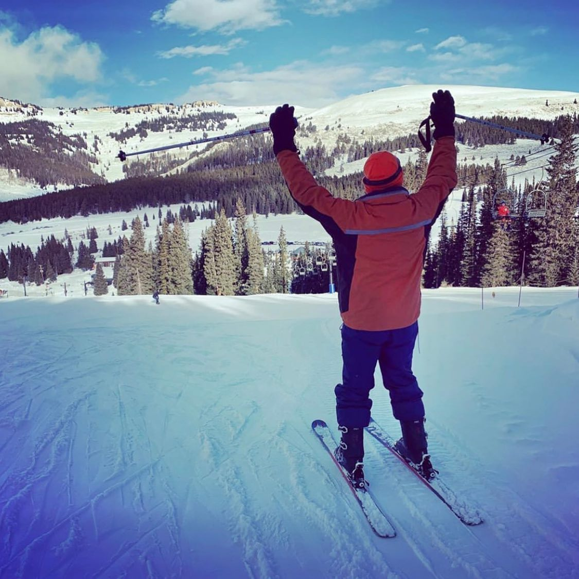 Image of a skier at the top of the slopes with their arms up at Antelope Butte Mountain Recreation Area