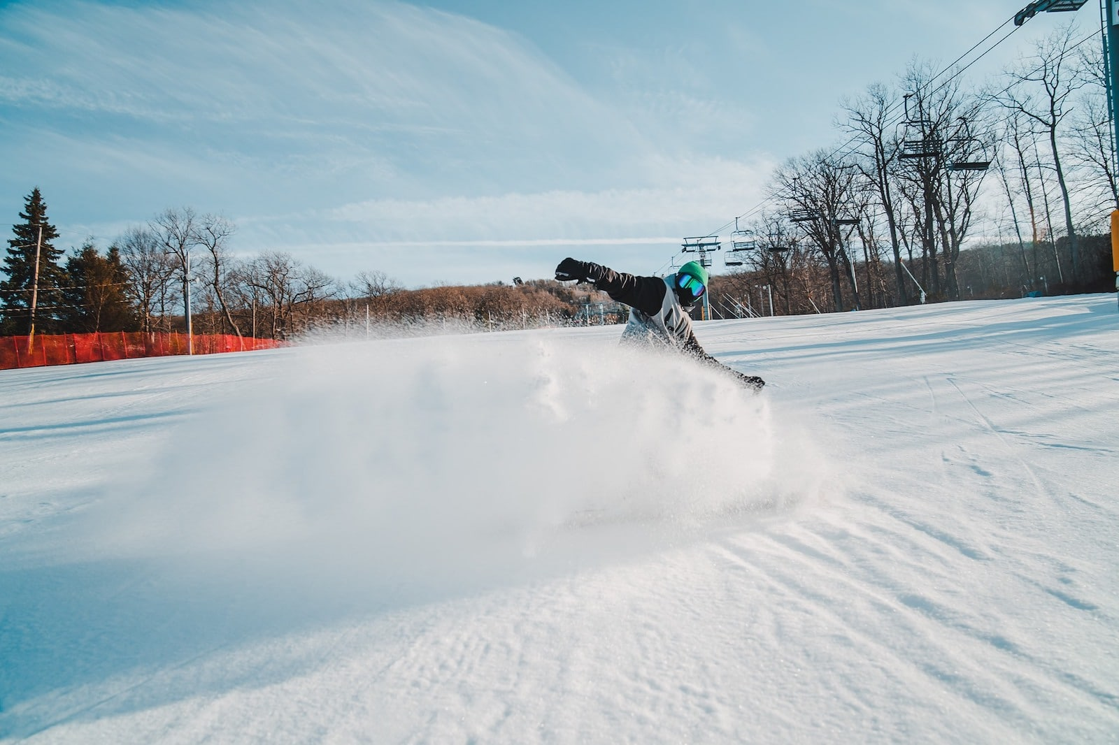 Image of a snowboarder whipping up powdery snow at Camelback Mountain in Pennsylvania
