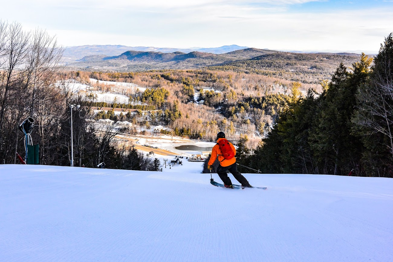 Image of a skier in orange going down the slopes at Crotched Mountain Resort in New Hampshire