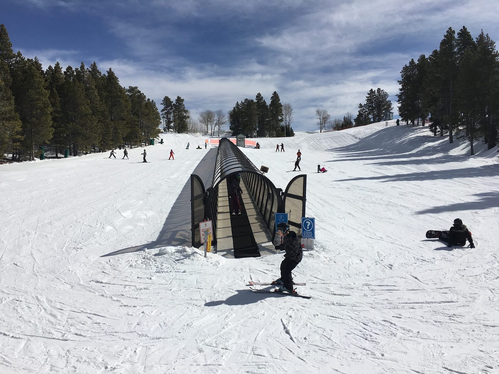 Image of skiers and snowboarders using the magic carpet on the beginner slope at Hogadon Basin Ski Area in Casper, Wyoming
