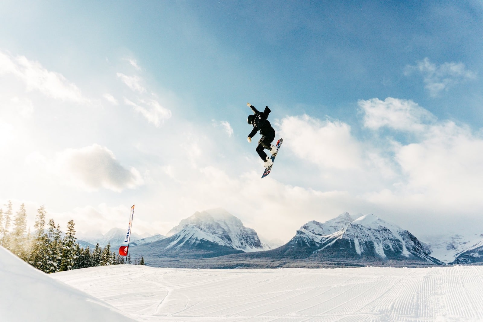Image of a snowboarder in black catching big air at Lake Louise Ski Resort in Canada