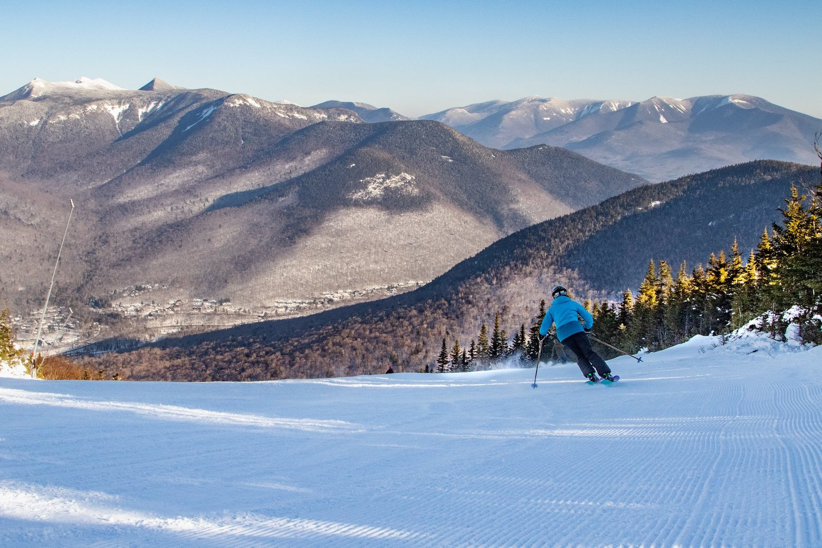 Skier in blue cruising across the snow at Loon Mountain Ski Resort in New Hampshire