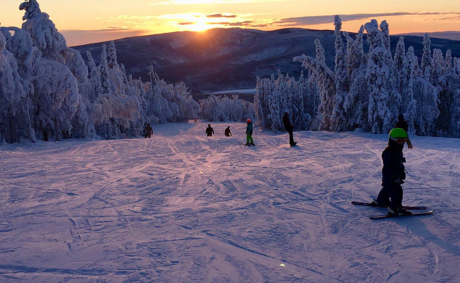Image of skiers at sunset at Moose Mountain Ski Resort in Alaska
