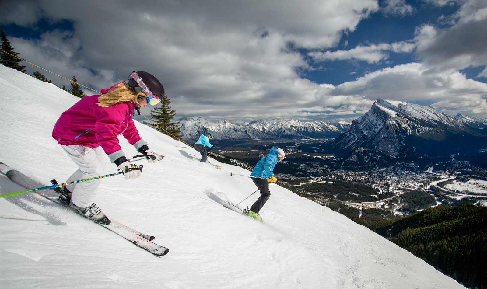 Image of skiers in pink and blue flying down the mountain at Mount Norquay in Canada