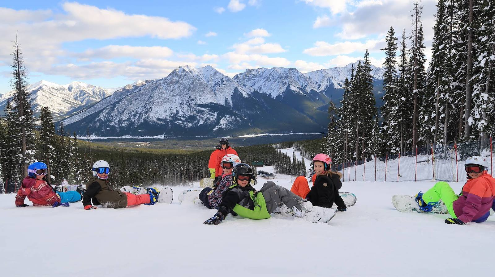 Image of seven snowboarders resting on the slopes at Nakiska Ski Area in Canada
