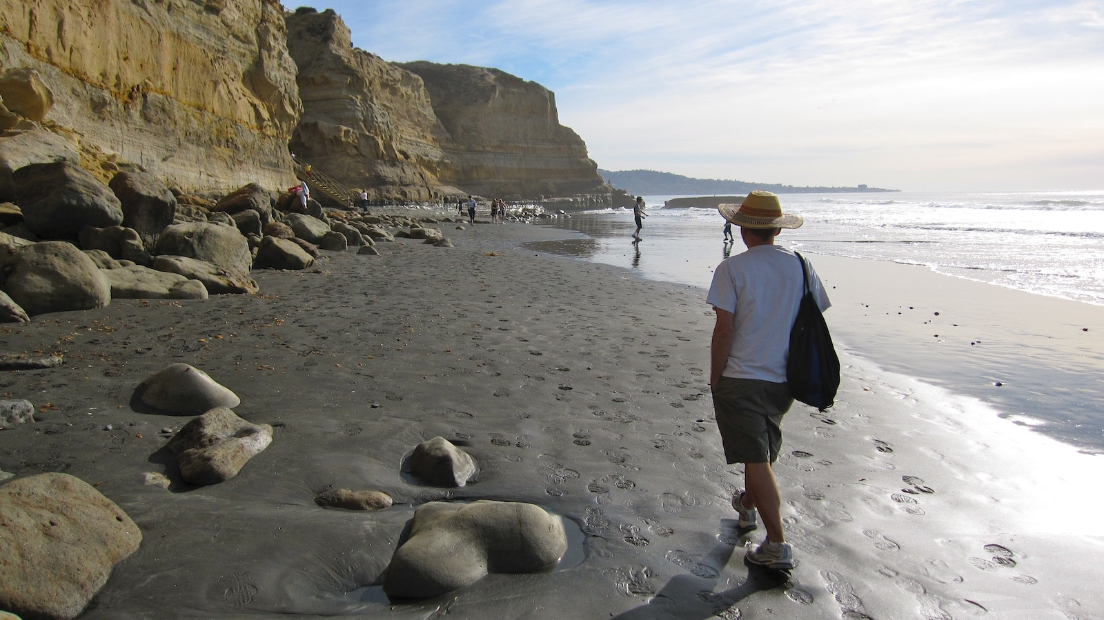 Image of a man walking along the Torrey Pines State Beach, California