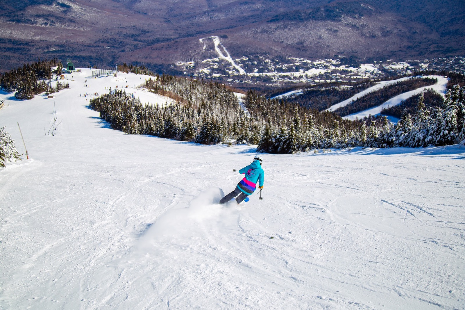 Image of a skier in bright blue and pink tearing up the slopes at Waterville Valley Resort, in New Hampshire