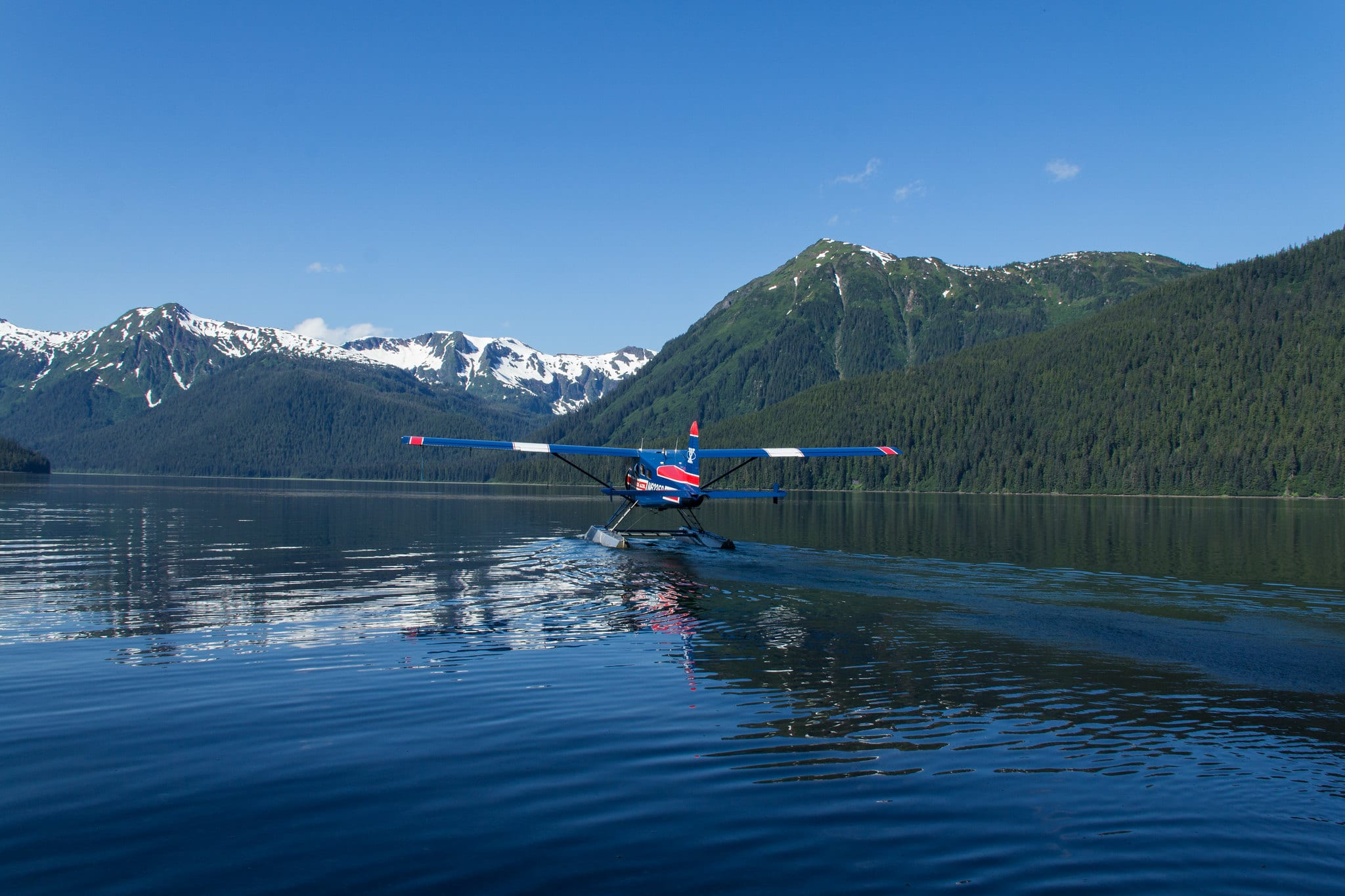 Image of a floatplane taking off on the water to shelokum hot springs in alaska