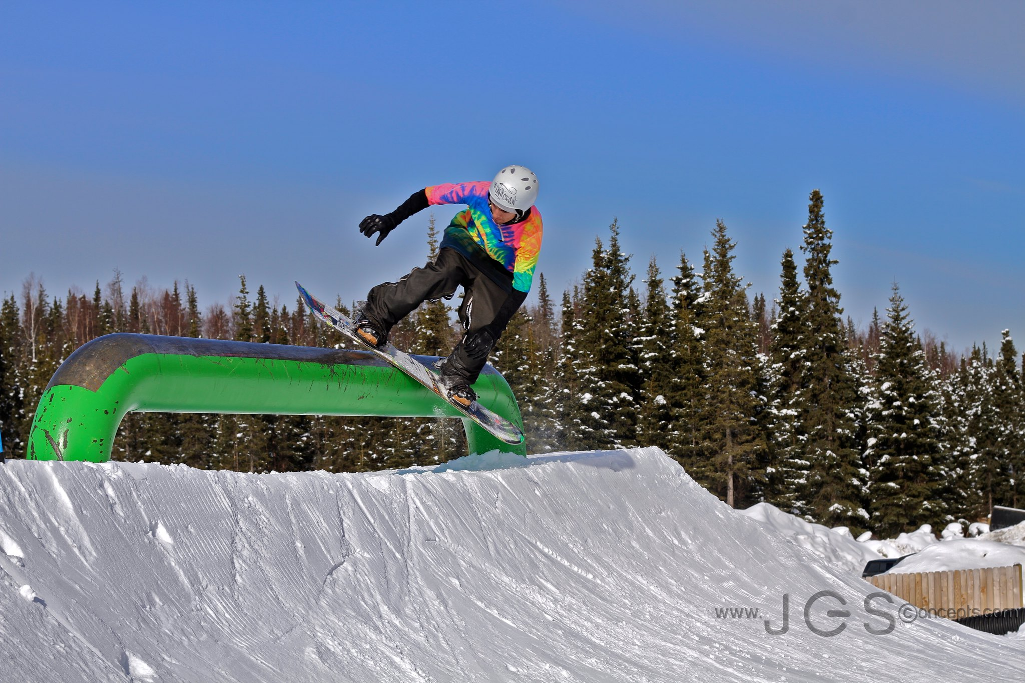 Image of a snowboarder in rainbow grinding the rail at Hilltop Ski Area in Alaska