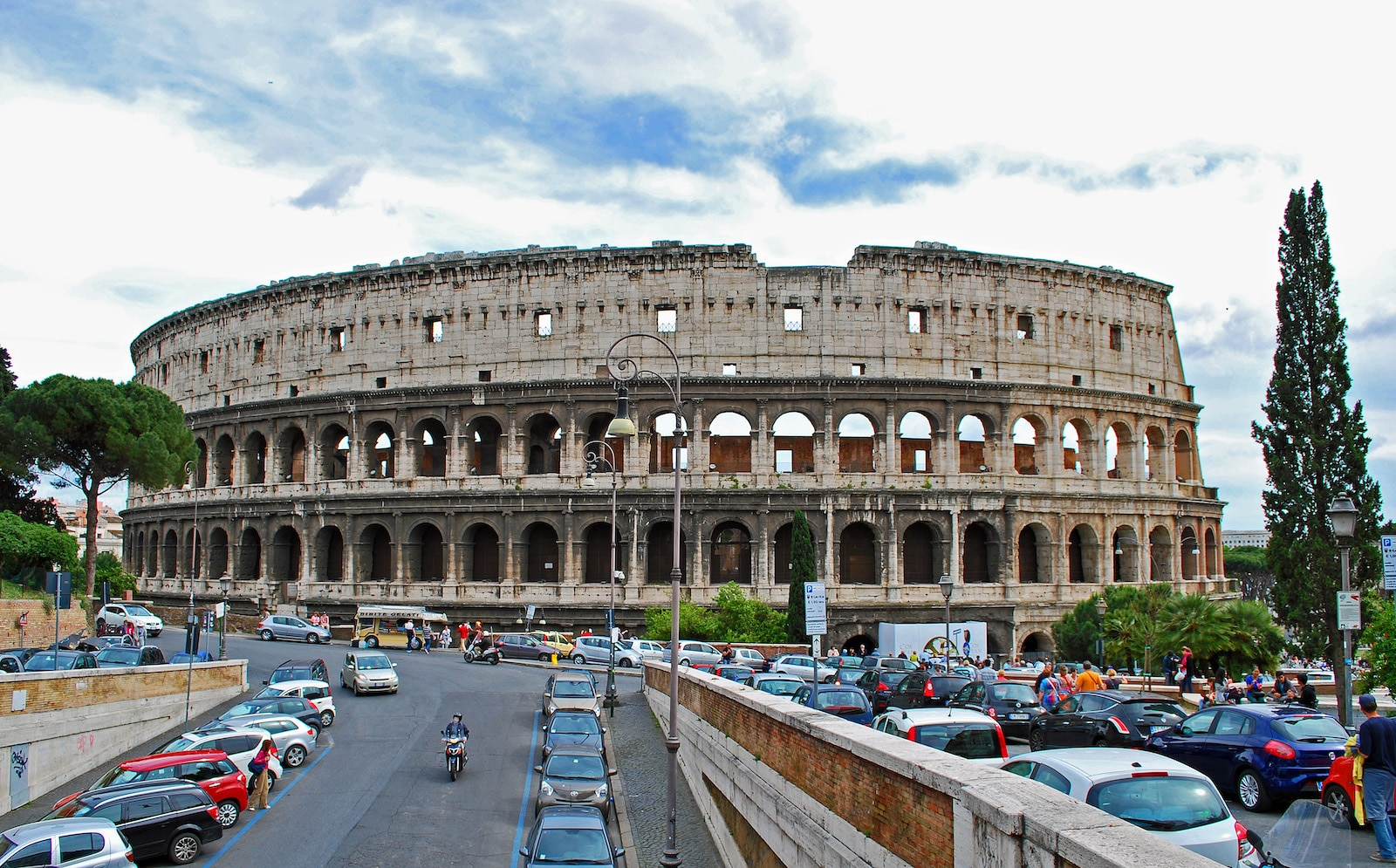 Colosseum in Italy with Road leading up to lined with cars