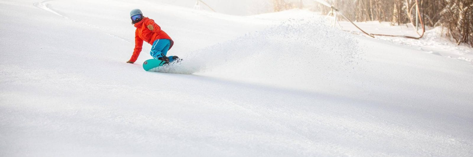 Image of a snowboarder in orange hitting the slopes at Killington Resort in Vermont